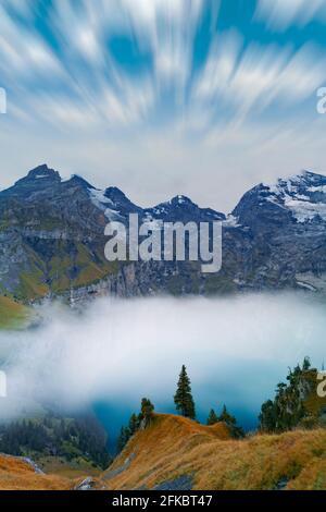 Nubes en el cielo sobre el lago Oeschinensee cubierto de niebla, Bernese Oberland, Kandersteg, cantón de Berna, Suiza, Europa Foto de stock