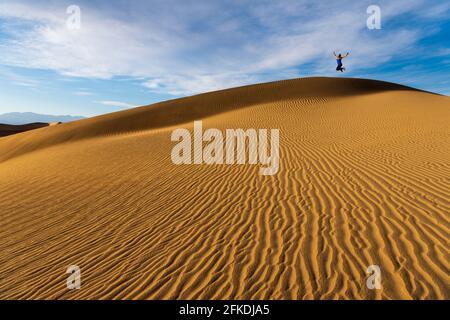 Una mujer en las prístinas ondulaciones de arena en Mesquite Dunas de arena en el Parque Nacional del Valle de la Muerte