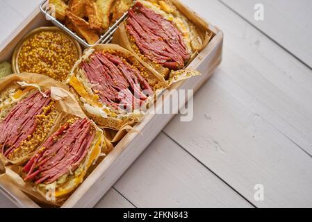 Enormes sándwiches con carne de pastami en caja de madera. Servido con patatas al horno, encurtidos