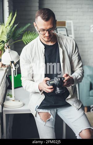El fotógrafo baldante está usando una cámara fotográfica en casa gafas mientras mira la pantalla