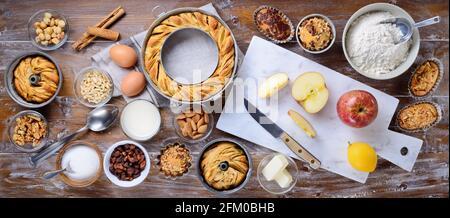Pasteles caseros, dulces horneados con ingredientes de cocina: Donuts de manzana, magdalenas y pasteles sobre fondo de madera. Vista de la mesa, plana. Foto de stock
