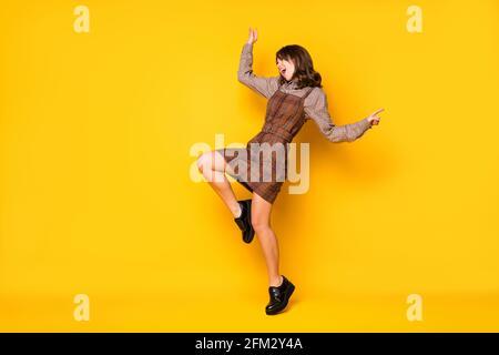 Foto de perfil a tamaño completo del baile de dama brunette gracioso optimista use sneakers de vestir aisladas sobre fondo amarillo vivo