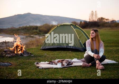 Descanse cerca de las montañas. Por la tarde, la joven se sienta cerca de una tienda y disfruta de las vistas a la montaña. La fogata está iluminada en el lado.