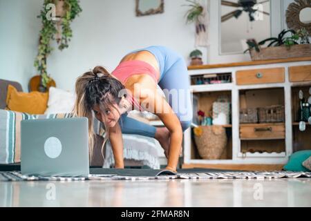 Mujer joven haciendo ejercicio en casa haciendo empujadores y mirando en su ordenador portátil personal para aprender o enseñar a hacer ejercicio - creador de contenido negocio libre de estilo de vida saludable concepto de la gente