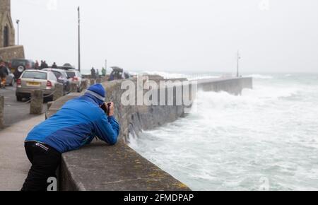 Porthleven,Cornwall,8th de mayo de 2021, un hombre toma fotos del mar áspero y de las grandes olas causadas por los vientos extremadamente fuertes en Porthleven, Cornwall. La temperatura fue de 12C, el pronóstico es para la lluvia y vientos fuertes en los próximos días.Crédito: Keith Larby/Alamy Live News