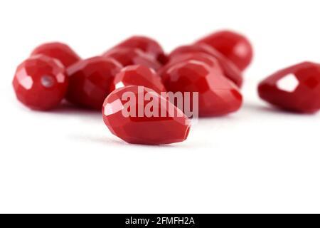 Forma de gota Cuentas rojas esparcidas sobre fondo blanco. Fondo o textura de beads.Close para arriba, usado en la ropa de la manera del acabado. Haga collar de la perla o stri