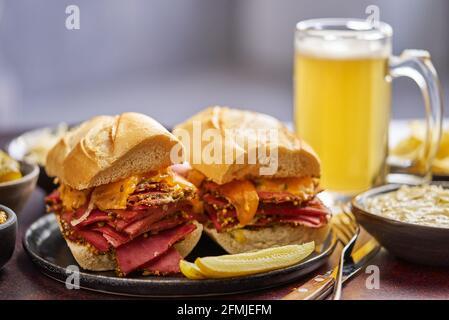 Deliciosos sándwiches de carne de pastami servidos con una copa de cerveza, encurtidos, patatas fritas y guarniciones.