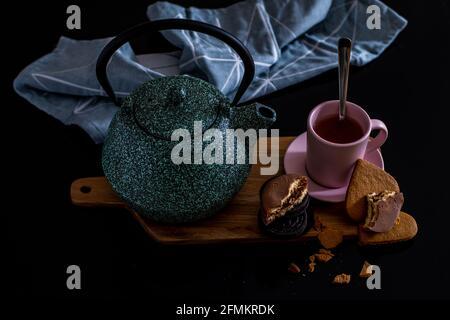 Día de San Valentín refrescante desayuno casero para la pareja con tetera verde cerámica, galletas de chocolate y galletas en forma de corazón con un aspecto vintage