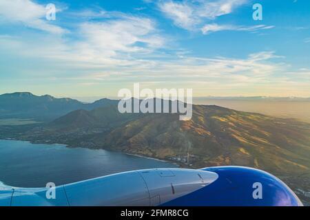 Vista de la isla tropical de O'ahu desde arriba ala durante la hora dorada