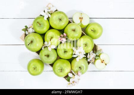 Manzanas frutas manzana verde caja de frutas sobre tabla de madera con hojas y flores de alimentos