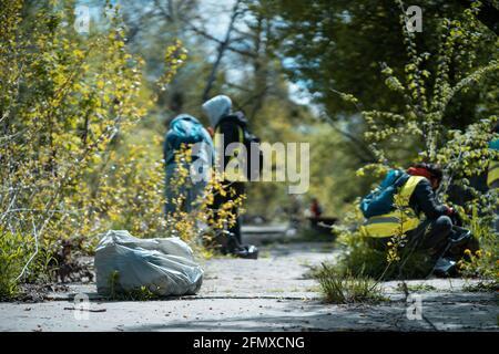 voluntarios limpiando el parque de la ciudad o el bosque de la basura plástica y basura