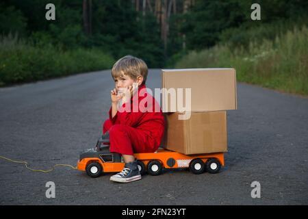 un lindo niño de cuatro años en un mono rojo se sienta en un gran coche de juguete - un camión con cajas de cartón - paquetes. Entrega de paquetes, pequeño cartero, camión driv