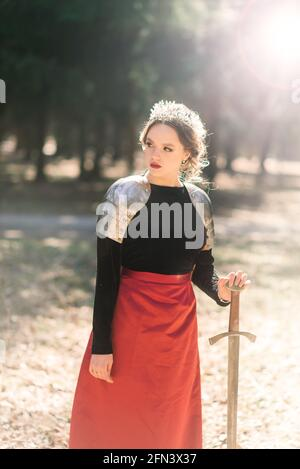 Mujer medieval armada guerrera en armadura posando mientras estaba de pie sobre el fondo del bosque y la puesta de sol.
