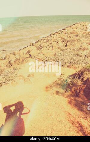 Fotografía de estilo Instagram en la silueta de un hombre tomando un paisaje marino por la tarde todavía de una costa rocosa, tomada Scarborough, Queensland, Australi