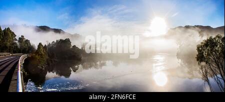 Paisaje panorámico panorámico de neblina a primera hora de la mañana en el lago Rosebery, en Tullah Tasmania, Australia, con el sol reventando sobre los picos de la montaña y la ref