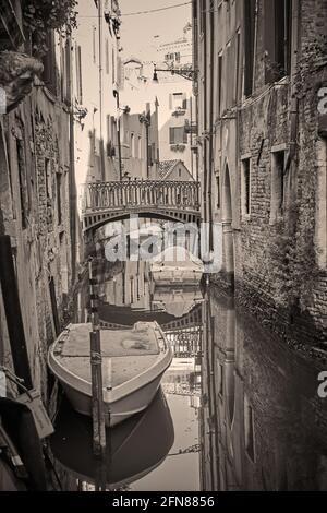 Canal en Venecia con puente y barcos, Italia. Fotografía de estilo vintage en blanco y negro, vista veneciana en tonos sepia