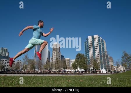 Hombre corredor activo correr al aire libre cerca de la ciudad.