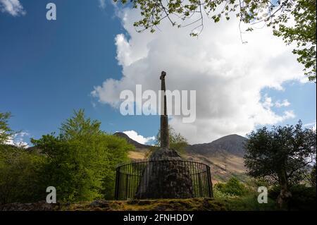 Glencoe Massacre Memorial cruce en Glencoe pueblo, Tierras Altas escocesas en un día soleado con cielo azul y nubes.