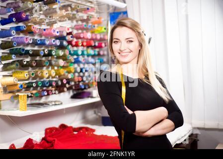 Hermosa mujer a medida sobre fondo de colores bobinas de hilo para costura y bordado.