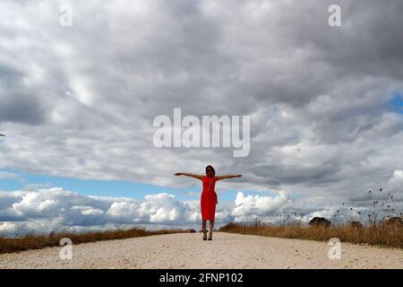 Mujer caminando sola por carretera recta. Cielo nublado. Francia.