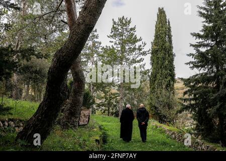 Laico y monje benedictino en el jardín de la basílica de San Pietro di Sores, Cerdeña, Italia