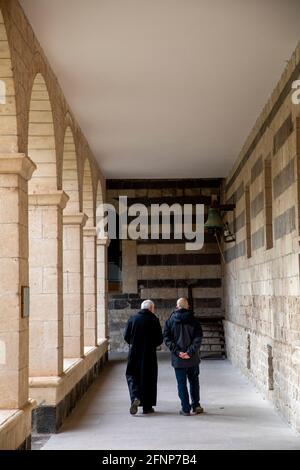Laico y monje benedictino en el claustro de la basílica de San Pietro di Sores, Cerdeña, Italia
