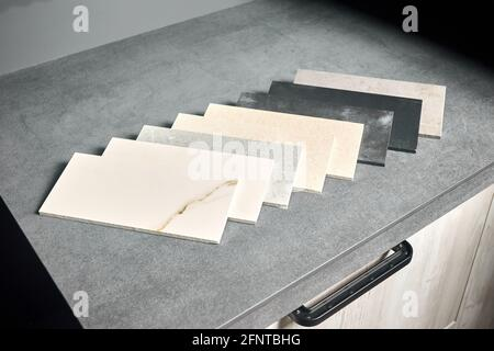 Muestras cuadradas de gres de porcelana colocadas en encimera de cocina como ejemplos de la fachada de la futura cocina. Expositor de gres de porcelana para