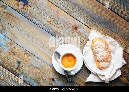 Vista desde arriba. Taza de café espresso italiano caliente y cruasanes sobre un fondo de madera rústica azul claro. Comida y bebida. Estilo de vida.