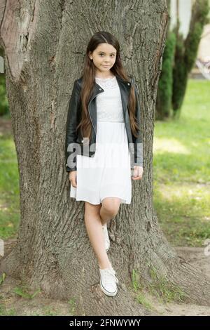 Lindo y moderno. Un niño pequeño está parado en el árbol en el parque. Aspecto de moda de pequeño modelo. Ropa y ropa de diseño para niños. Moda y estilo. Moda infantil y.