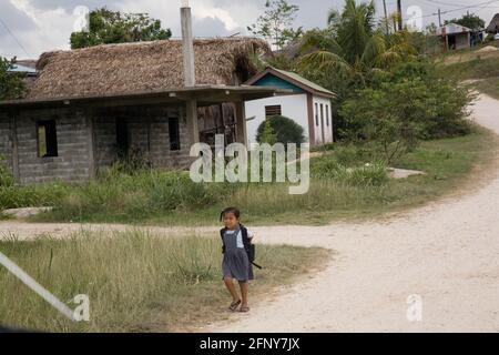 Una joven caminando a casa desde la escuela en la comunidad maya de San Miguel, Toledo, Belice