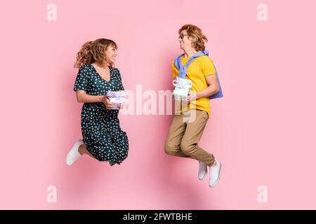 Foto de perfil a tamaño completo de pareja optimista divertido salto de retención presente ropa de vestir colorida aisladas sobre fondo rosa pastel