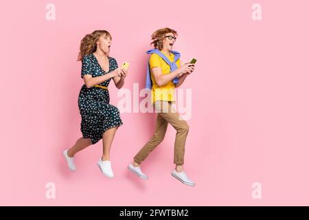 Foto de perfil a tamaño completo de la pareja optimista gracioso salto de mirada el teléfono lleva ropa colorida aislada sobre fondo rosa pastel