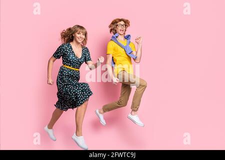 Foto de perfil a tamaño completo de la pareja optimista divertida ropa de correr ropa colorida aislada sobre fondo rosa pastel