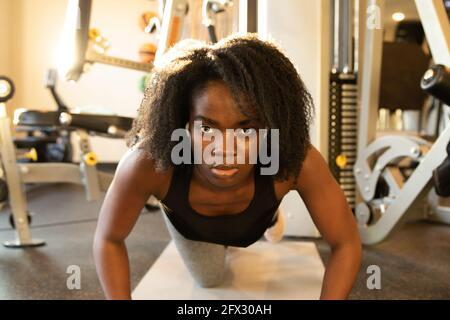Mujer joven haciendo flexiones sobre colchoneta de yoga. Primer plano, una persona, afroamericana, mujer negra, modelo africano, mujer natural del pelo, cara sonriente, woma del ajuste