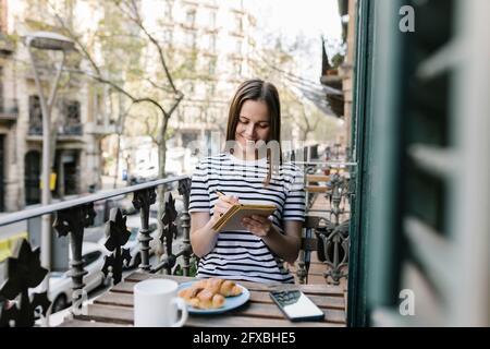 Hermosa mujer sonriendo mientras escribía en el diario en el balcón