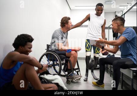 Feliz hombre amputado y atletas parapléjicos en el vestuario