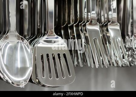 Foto de acero inoxidable varios utensilio de cocina colgando en el estante de la tienda.