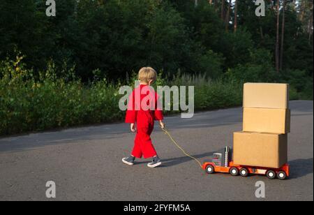 un niño en un mono rojo camina a lo largo de la carretera y lleva un coche de juguete grande - un camión con cajas de cartón en él. Poco mensajero en el trabajo. Entrega de paquetes,