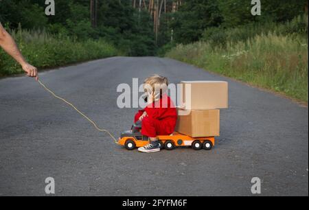 el niño en monos rojos se sienta en un gran coche de juguete - un camión con cajas de cartón, hablando por teléfono. Entrega de paquetes, pequeño cartero. Como papá. Un hombre