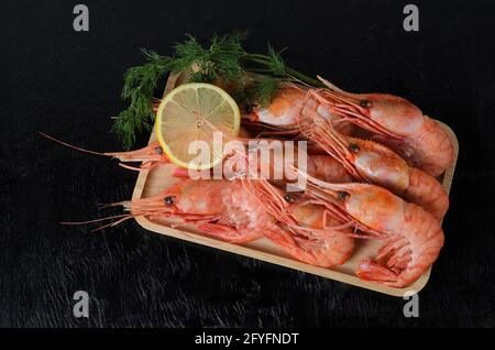 Gambas hervidas en una concha con eneldo y limón en un tazón de madera sobre un fondo de madera oscura. Enfoque selectivo.