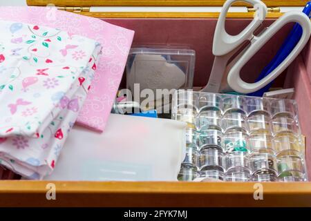 Selección de accesorios de costura en una caja de costura, con tejido rosa