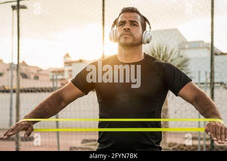 Hombre latino haciendo ejercicios de entrenamiento sesión al atardecer - Joven hispano entrenando duro mientras escucha música con auriculares