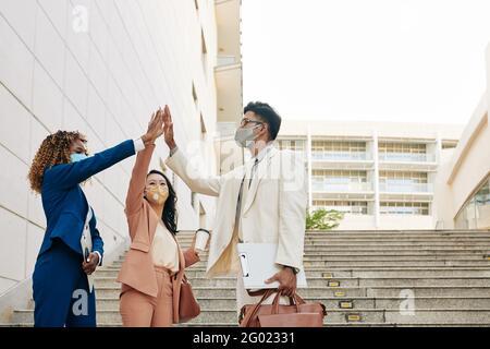 Grupo de gente feliz de negocios emocionados en máscaras médicas de pie al aire libre y dándose unos a otros cinco altos después de terminar el trabajo en proyecto grande