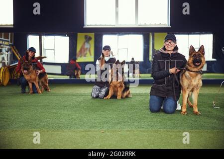 Tres mujeres y sus perros en la escuela de obediencia