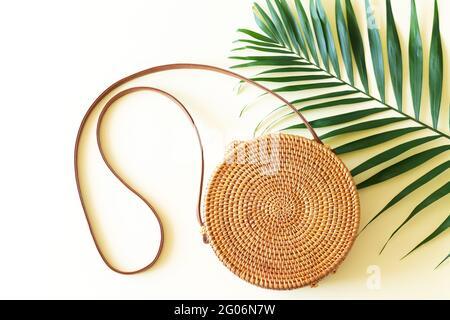 Moderna bolsa redonda de paja de ratán y vista superior de hojas de palma tropical