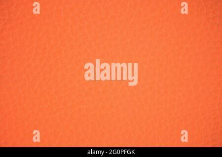 La superficie rugosa de cuero auténtico pintado en un color naranja brillante. Fondo, patrón, textura.