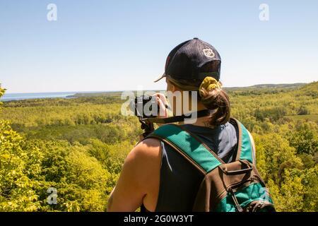 TOBERMORY, CANADÁ - 30 de mayo de 2021: Una mujer toma una foto de un mirador en la bahía georgiana - fotografía temática del turismo editorial.