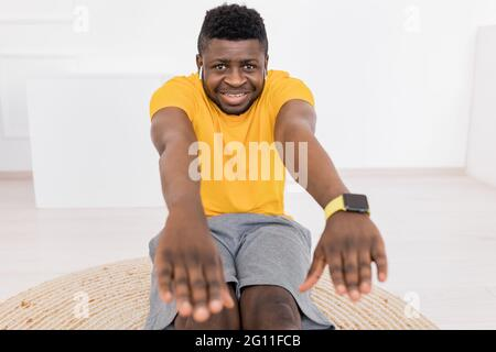 Hombre afroamericano deportivo que estira los músculos de la pierna y la espalda delante de la cámara, mira la cámara y escucha música, calentando en casa
