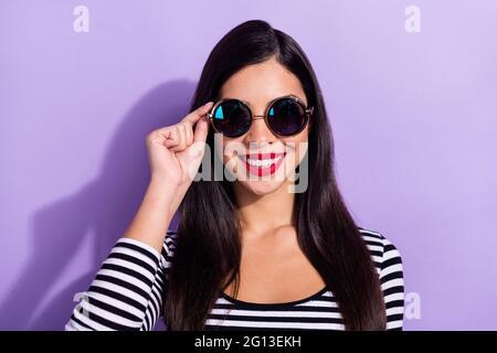 Foto de encantadora dulce joven mujer vestida vestido a rayas conjunto brazo gafas oscuras sonriendo aislado color violeta fondo