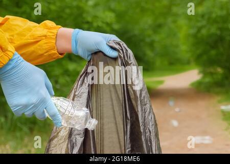 Las manos voluntarias recogen la basura plástica de la hierba en el parque. Limpieza voluntaria de basura en un bosque. Residuos plásticos. El hombre recoge gente de la basura